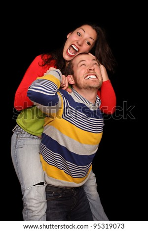 playful young couple in front of black background fighting for fun - stock photo