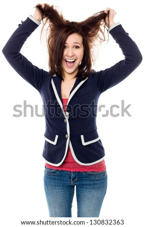 Playful young female pulling out her hair in madness. Isolated studio shot. - stock photo