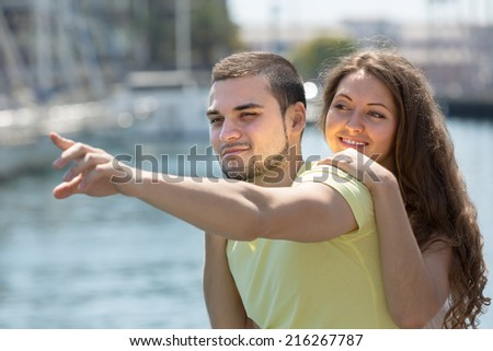 Playful young girl and her boyfriend smiling against sea - stock photo
