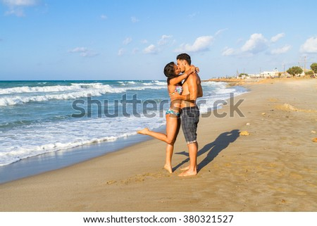 Playfull young couple in bikini and shorts at the beach. - stock photo