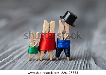 Playground family. Abstract: The family of linen clothespins. Man, woman with child. Vintage paper background. Soft focus. - stock photo