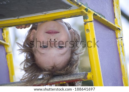 Playground fun: cute kid upside down on monkey bar - stock photo