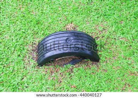 Playground rainy day, grass car tire - stock photo