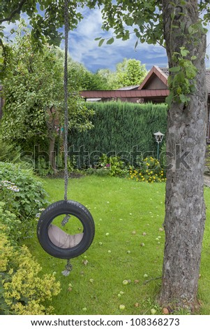 playground with a self made garden swing hanging on a tree - stock photo