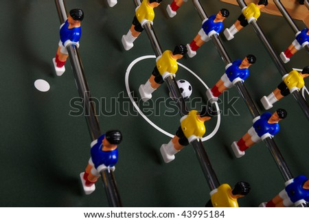 Playing a table foosball game - stock photo