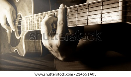 Playing acoustic guitar,guitarist or musician in sepia filtered color. - stock photo