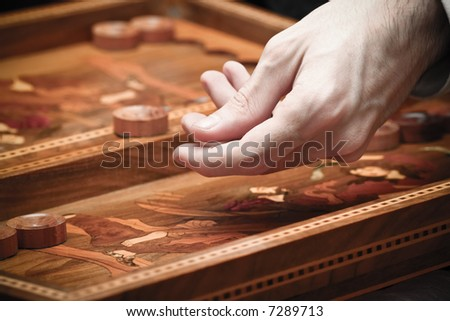 playing backgammon - focus on the hand with vintage effect - stock photo