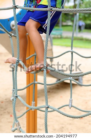 playing barefoot on a rope climbing equipment playground - stock photo