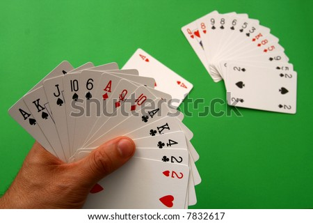 "playing bridge - one hand (A,K,J,10,6 spades, 2 heart, A,Q,10 diamonds, A,K,4,2 clubs),  on table other ""bridge hand""  and lead Ace heart,  background green, selective focus - stock photo"
