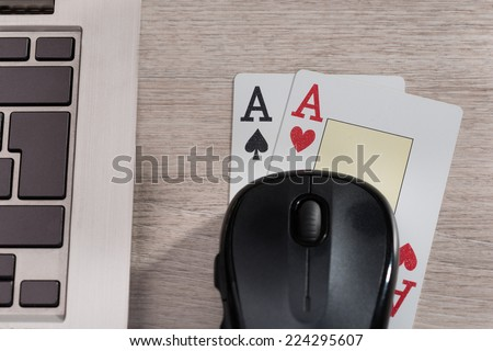 Playing cards and computer in online gaming concept - stock photo