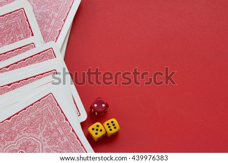 Playing cards and dices on red background. Set of playing card and three dices on a matte red table. Gambling concept with place for text. - stock photo