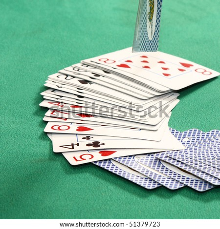Playing cards on green table - stock photo