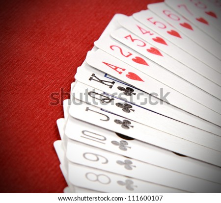 playing cards on red poker table - stock photo