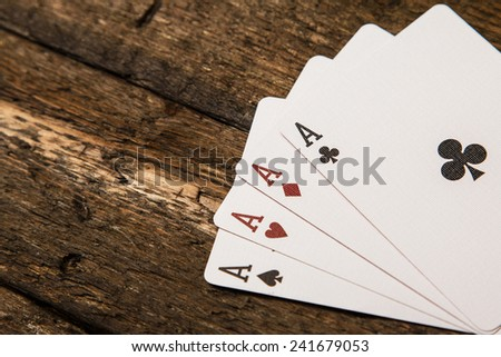 Playing cards on wooden surface - stock photo