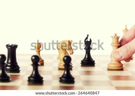 Playing chess game - moving the white queen - stock photo