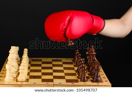 Playing chess in boxing gloves isolated on black - stock photo