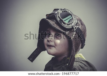 playing, fun and funny child dressed in aviator hat and goggles - stock photo