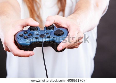 Playing games concept. Part body man with joystick play game on console playstation. Male hands holding grey pad. - stock photo