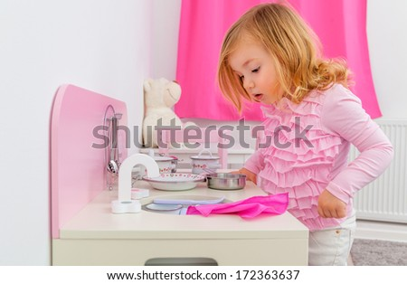 playing girl in her kitchen - stock photo
