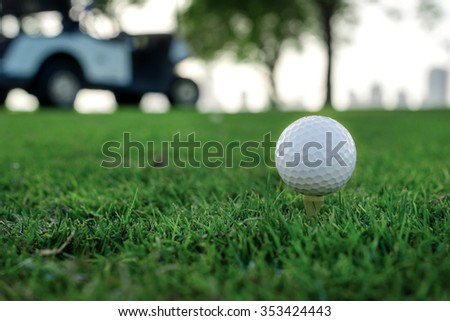 Playing golf and a golf cart. Golf ball is on the tee for a golf ball on the green grass of the golf course against the background the city's skyscrapers and golf carts - stock photo