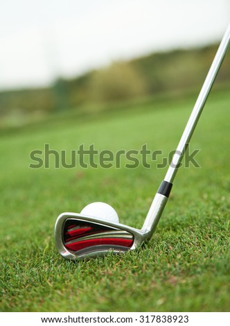 Playing golf, ball on tee and golf club about to shot. - stock photo