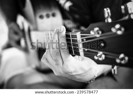 Playing guitar close up. selective focus image (Black and white) - stock photo