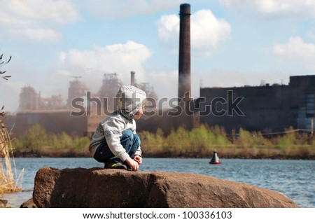 Playing little boy on the river coast in front of metallurgy plant - stock photo