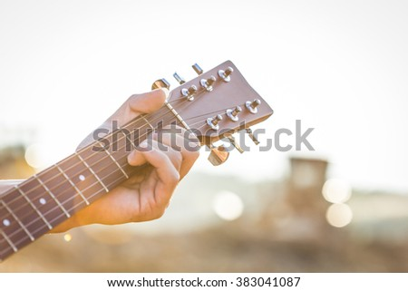Playing on acoustic guitar outdoor,closeup - stock photo