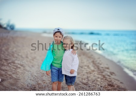 playing on the seashore small girl with long hair and a boy in a cap - stock photo