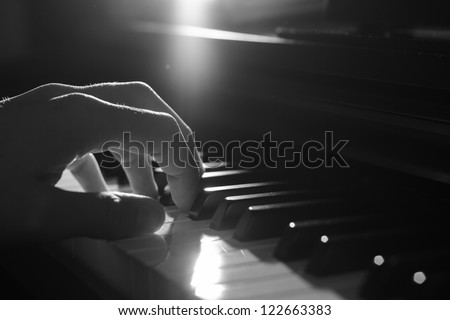 Playing piano - dramatic light, B&W - stock photo
