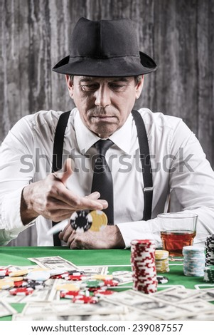 Playing poker. Serious senior man in shirt and suspenders throwing his gambling chips at the poker table  - stock photo