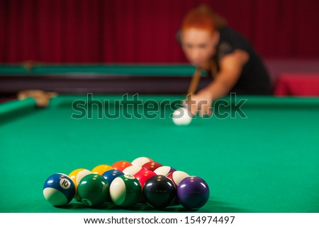 Playing pool. Confident young man aiming the billiard ball with cue - stock photo