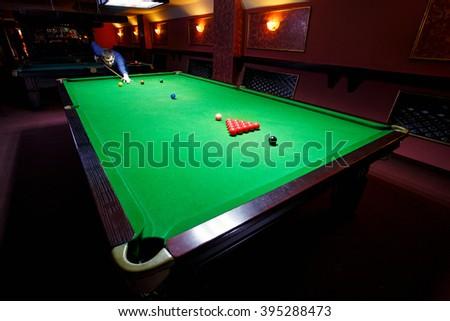 Playing pool, man aiming the billiard ball, snooker - stock photo