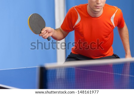 Playing table tennis. Confident young men playing table tennis - stock photo