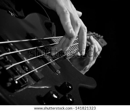playing the guitar: closeup of hands and strings, black and white - stock photo