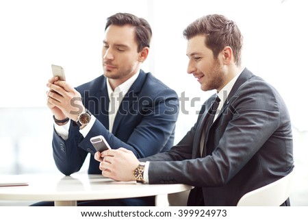 Pleasant business men using mobile phones - stock photo