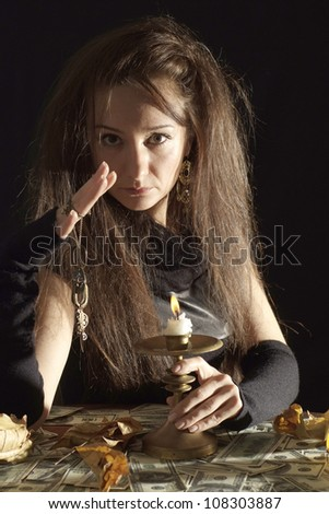 Pleasant girl as a witch on a dark background - stock photo