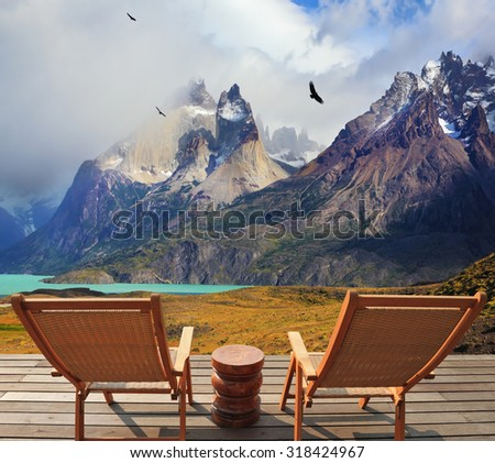 Pleasant holiday in Chile. Wooden chairs in the park Torres del Paine. On the horizon is visible snow-covered rocky mountain - stock photo