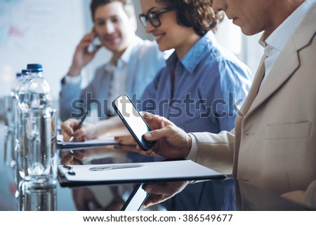 Pleasant man holding mobile phone - stock photo