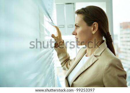 Pleasant midage business woman looking outside through jalousie - stock photo