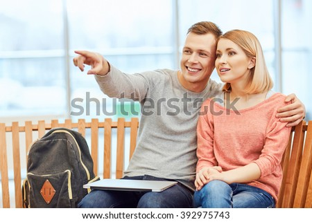 Pleasant students sitting on the bench  - stock photo