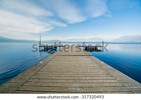 Pleasant view from a wooden jetty, calm lake water, horizon and Alps mountains in the background. Viverone lake in Piedmont, Italy - stock photo