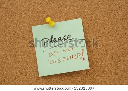 Please do not disturb words written on paper and pinned on cork board - stock photo