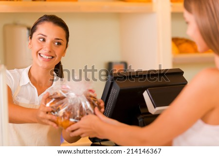 Please enjoy! Beautiful young female baker giving cookies to customer and smiling  - stock photo