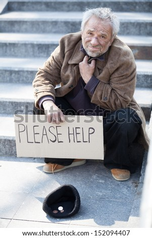 Please help. Depressed senior tramp in dirty wear sitting on stairs and holding poster - stock photo