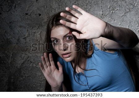 Please no! Terrified young woman looking at camera and stretching out hand while leaning at the dark wall - stock photo