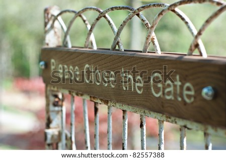 Please open the gate sign on an iron gate with wood - stock photo