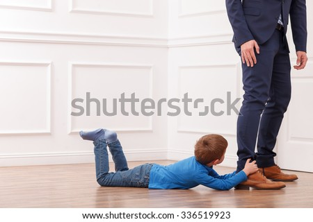 Please stay with me. Small boy is lying on floor and holding the legs of his father with efforts. Copy space in left side - stock photo