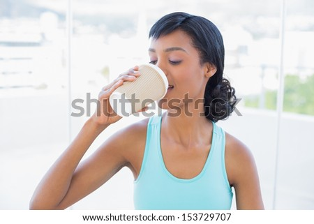 Pleased black haired woman drinking coffee in a living room - stock photo