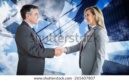Pleased businessman shaking the hand of content businesswoman against skyscraper - stock photo